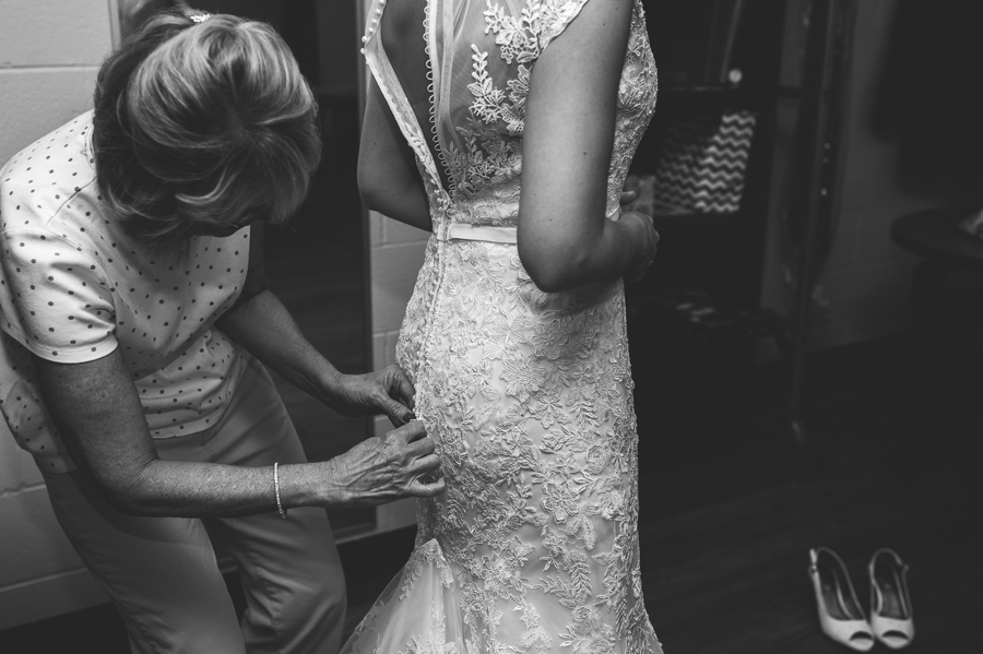 mother of bride helping bride get dressed