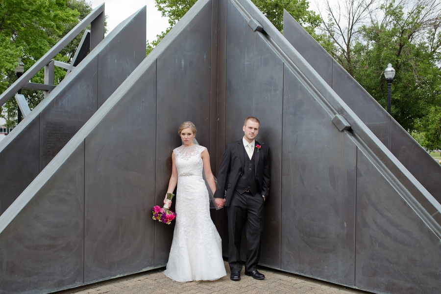 bride and groom leaning on architecture