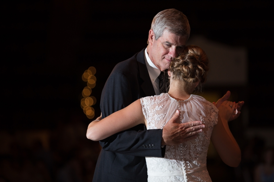 father hugging bride during dance