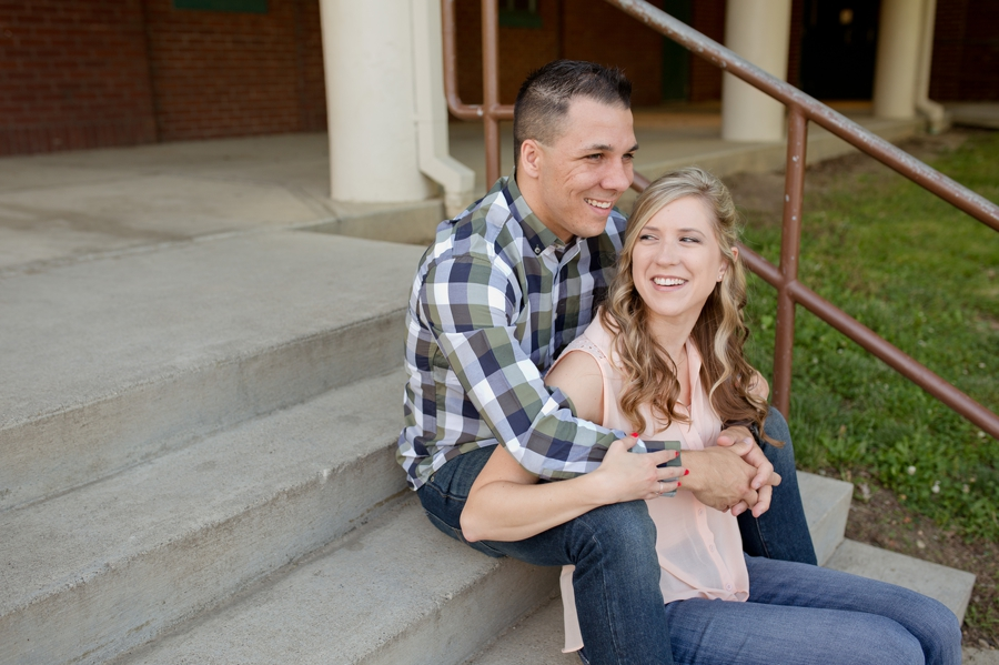 engaged couple laughing on stairs at park