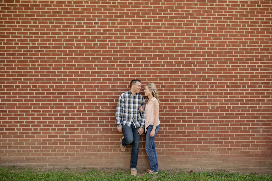 engaged couple leaning on brick wall