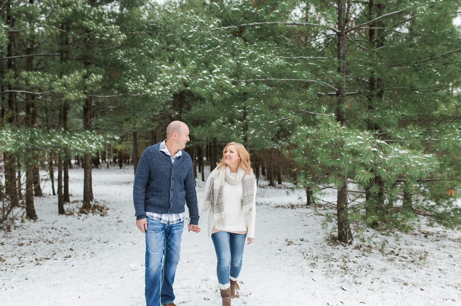 engaged couple walking in snow