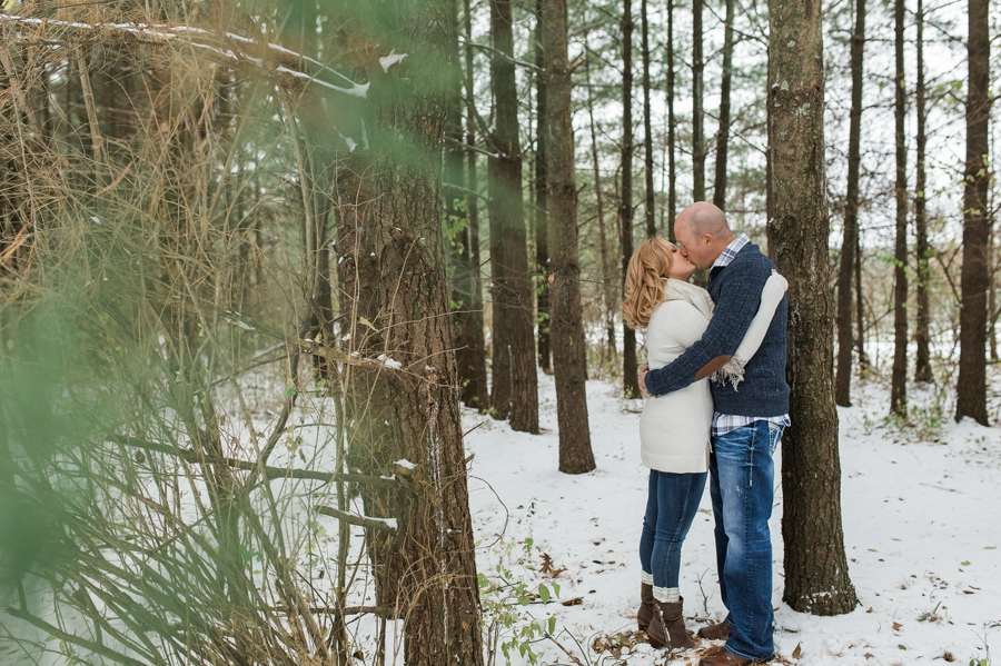 engaged couple kissing in woods