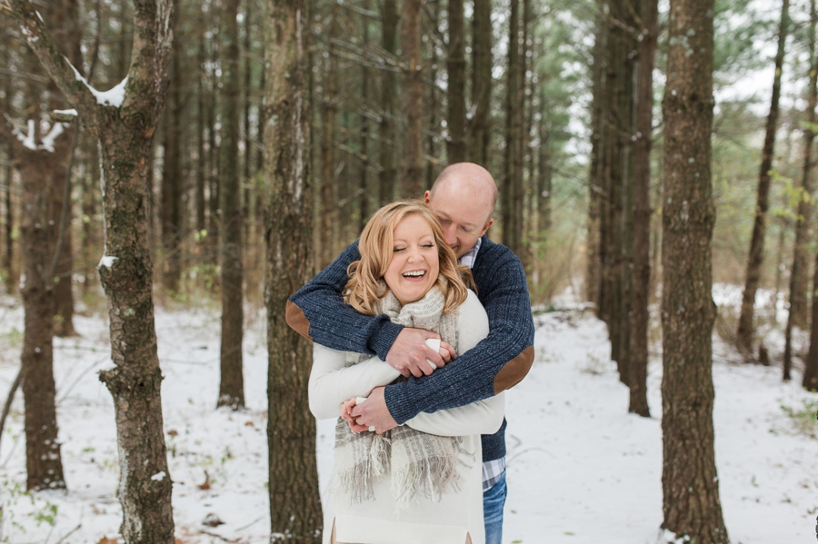 engaged couple laughing in woods