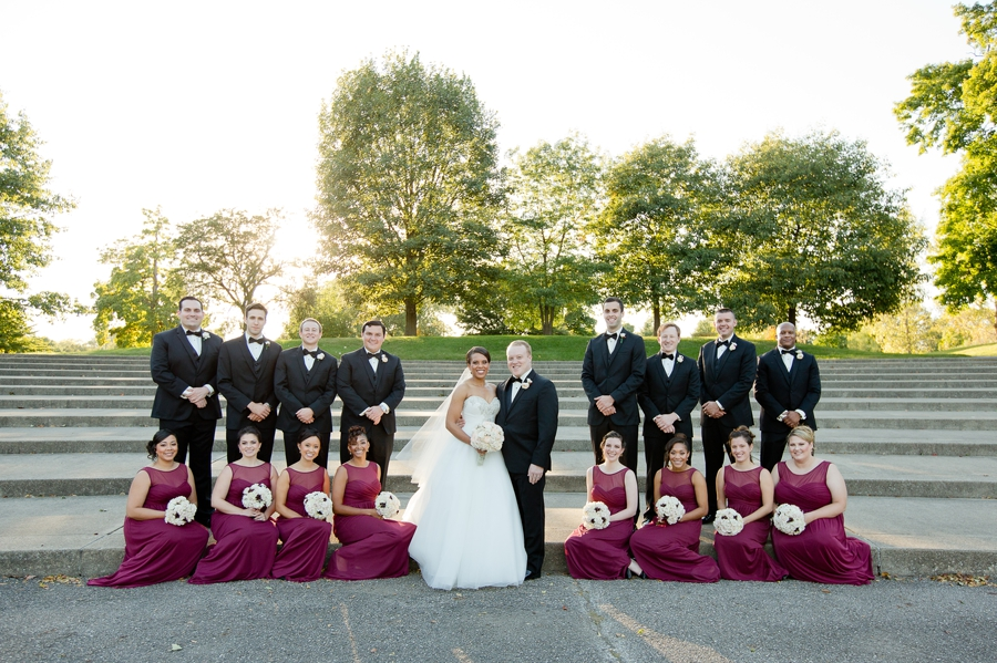 bridesmaids sitting groomsmen standing at sunset