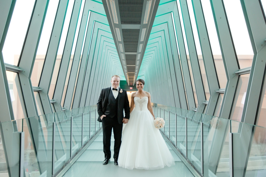 married couple smiling looking at camera on skybridge