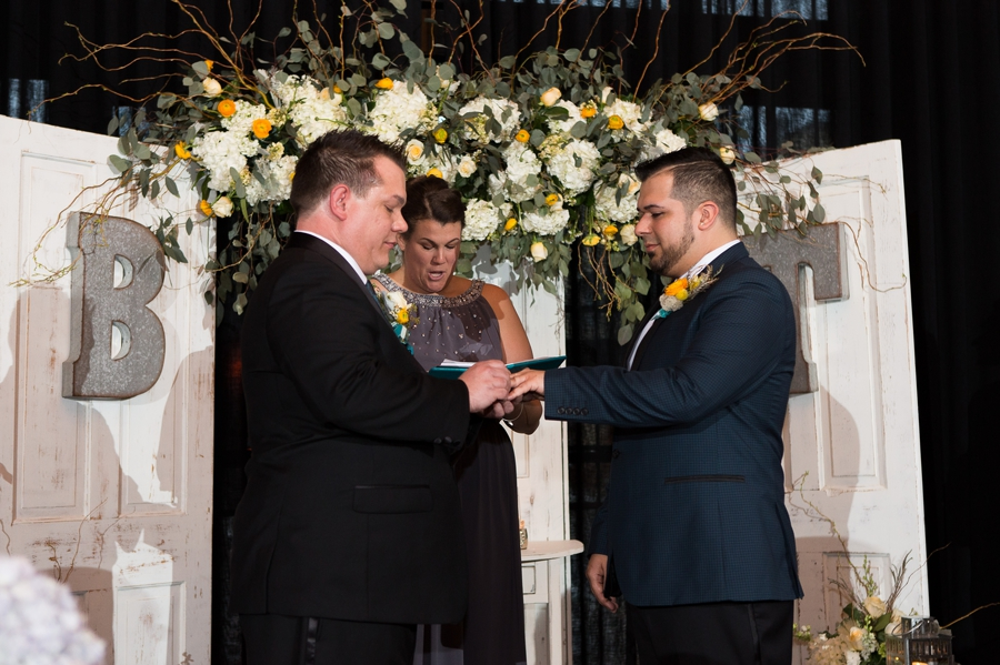 same sex couple exchanging rings