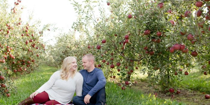 engaged couple smiling at each other at apple orchard