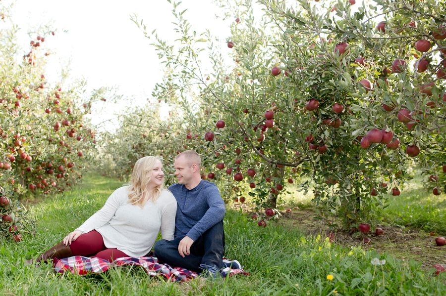 engaged couple smiling at each other at Lynd's Fruit Farm