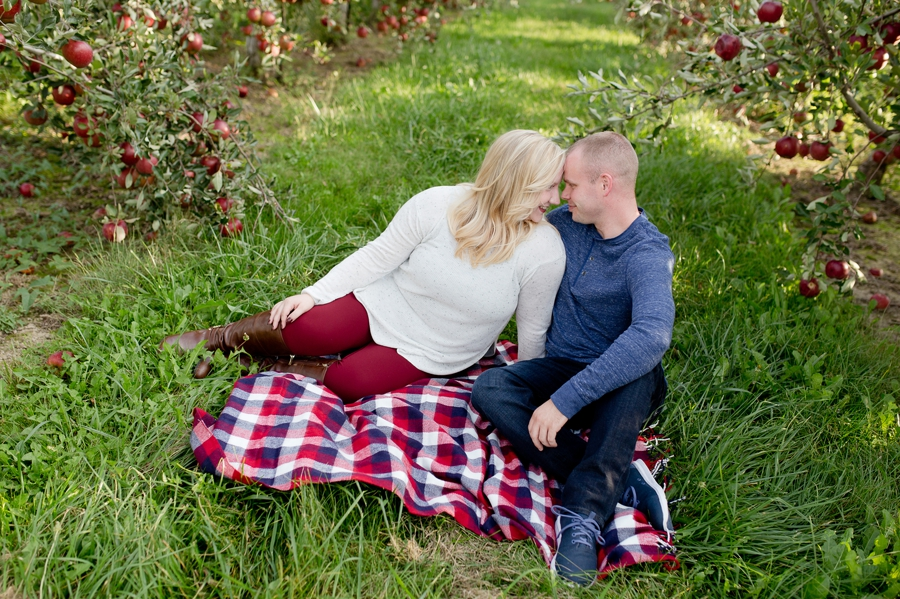 engaged couple with foreheads together at Lynd's Fruit Farm