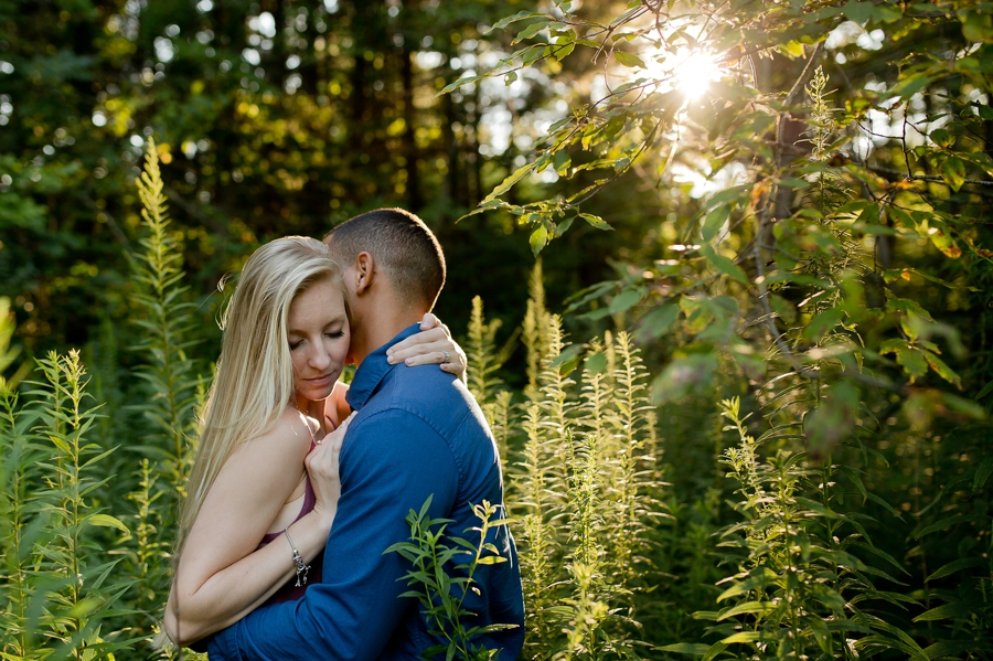 engaged couple hugging in field