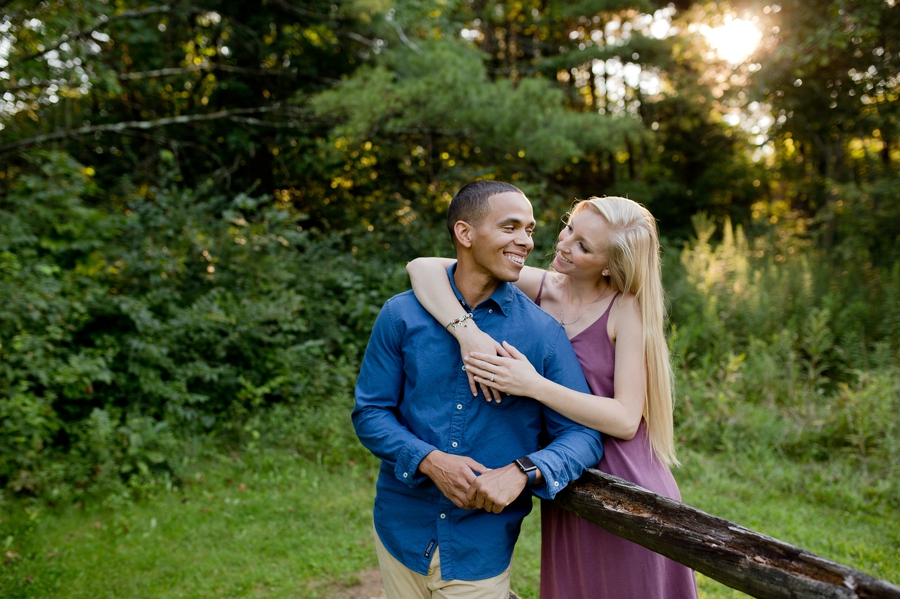 engaged couple leaning on fence at Slate Run Farm