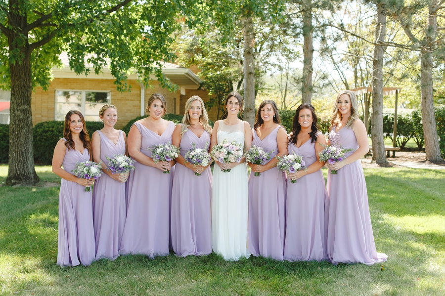 bride with bridemaids in lavender dresses at Rustic Barn Wedding