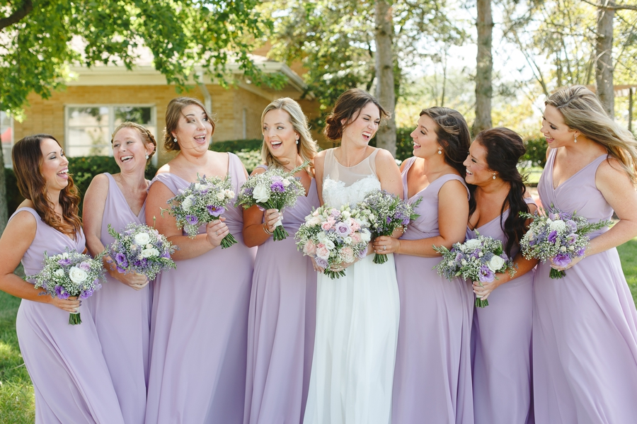 bride and bridemaids laughing at each other at Rustic Barn Wedding