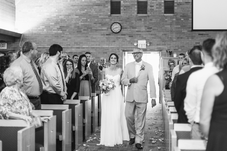 black and white photo of bride walking down aisle of church