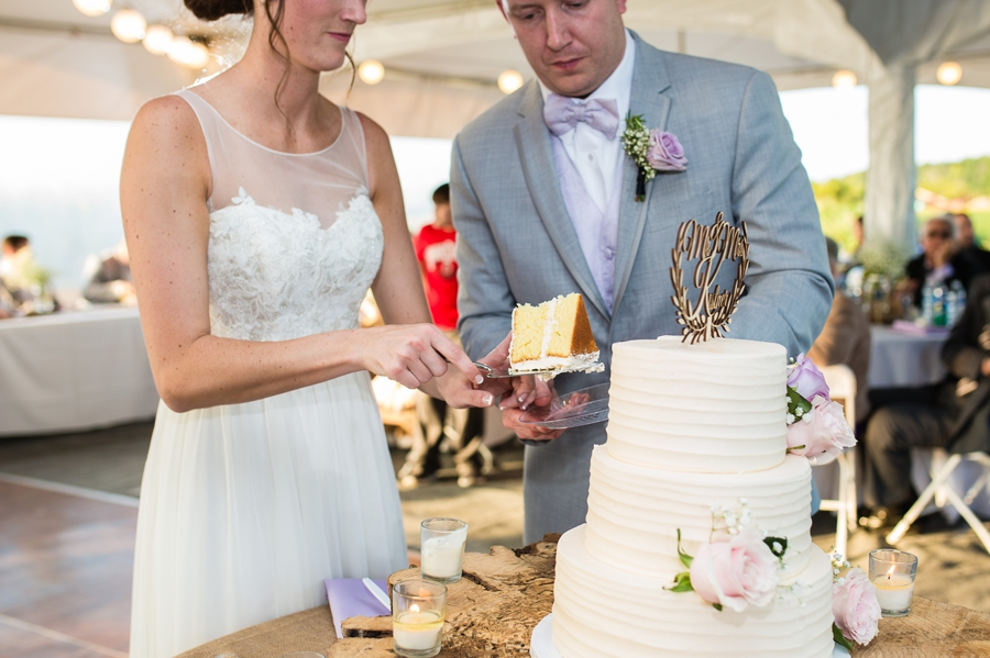 close up of cake cutting by bride and groom