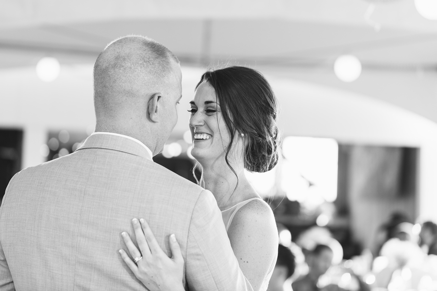 black and white photo of bride laughing at groom during first dance