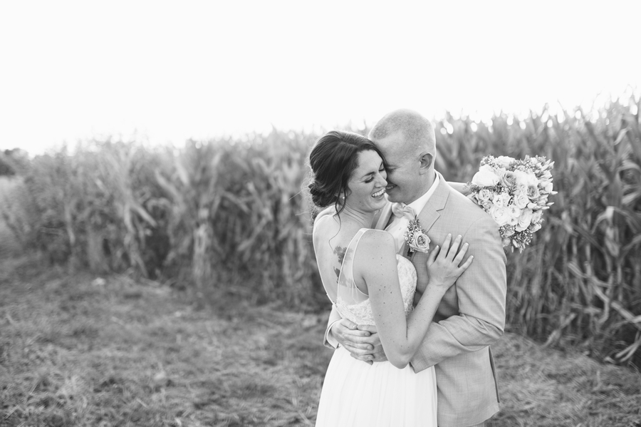 black and white photo of couple laughing by corn field