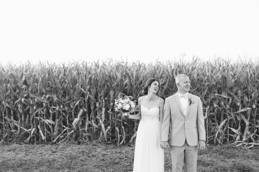 black and white photo of couple in front of field at Rustic Barn Wedding