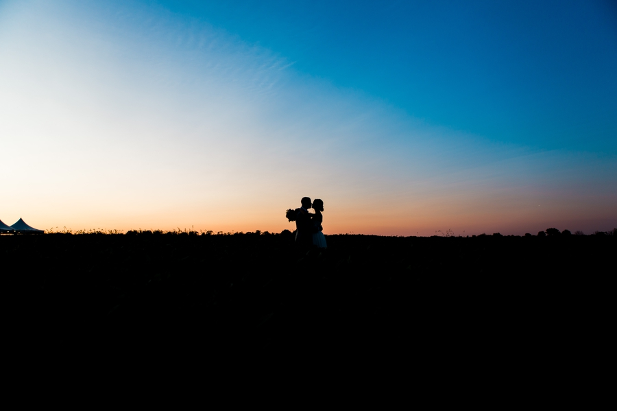 wide silhouette photo of bride and groom kissing in field at Rustic Barn Wedding