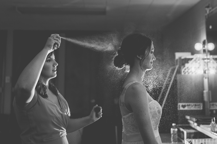 black and white photo of bride getting hairspray in hair