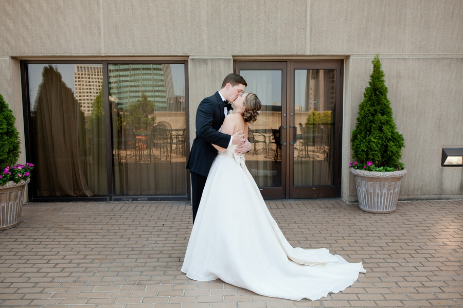 bride and groom kissing on rooftop at statehouse
