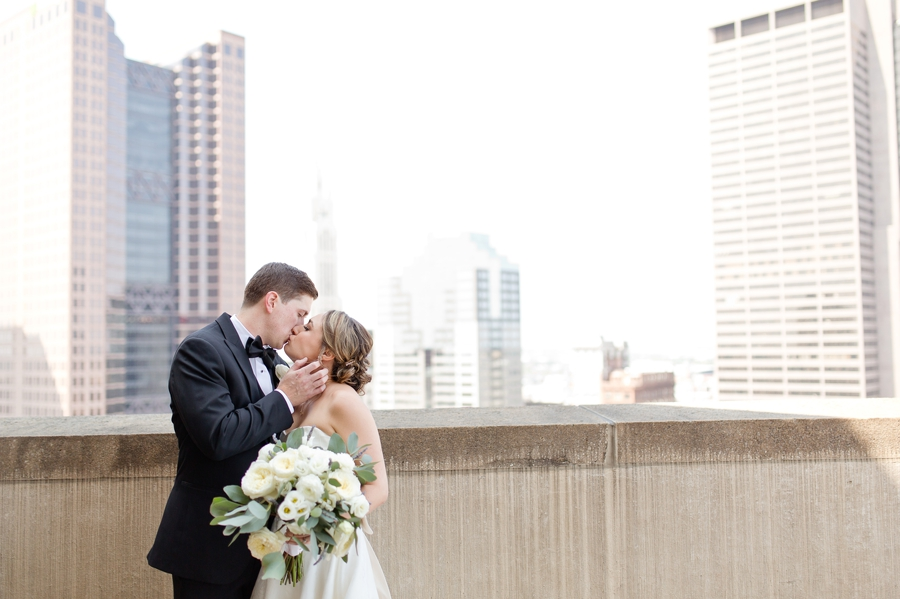 bride and groom kissing on rooftop at ohio statehouse wedding