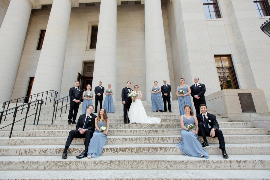 wide photo of wedding party on stairs at ohio statehouse