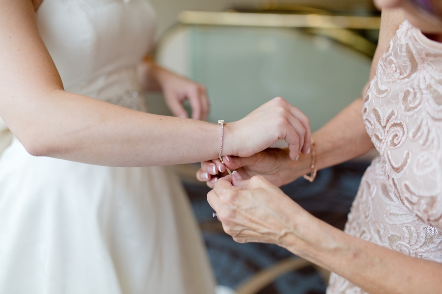 mother of bride putting on brides jewelry at statehouse