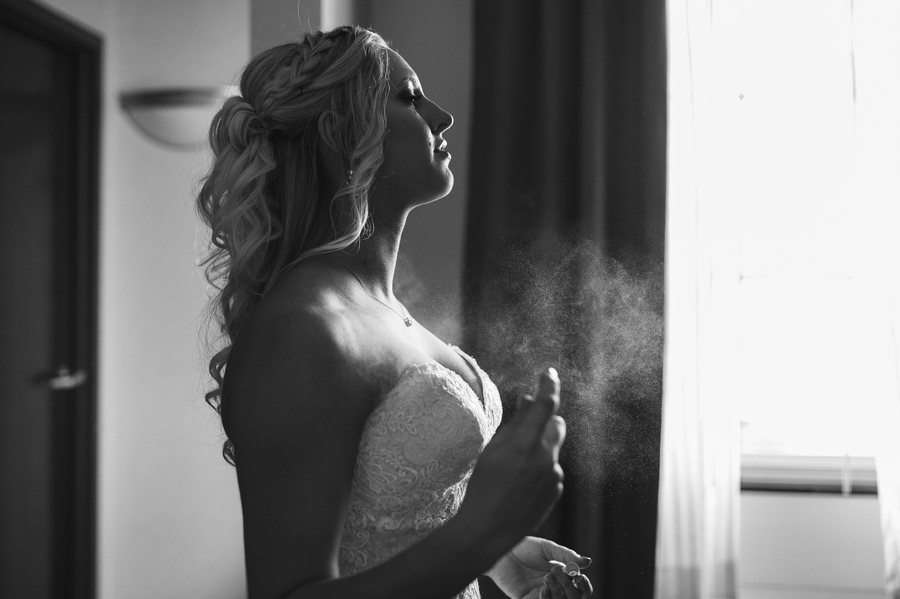 bride spraying perfume on before her barn wedding in ohio