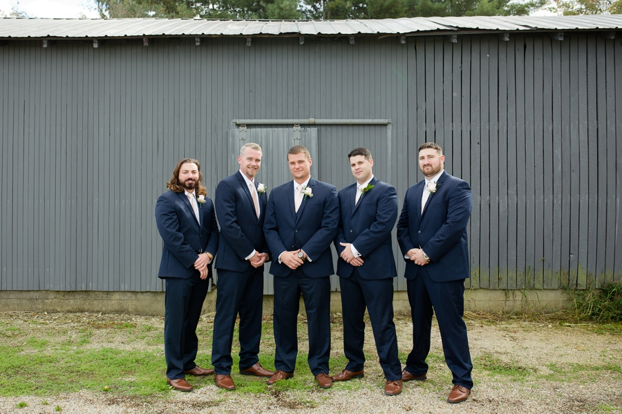 groom with groomsmen smiling at a barn wedding