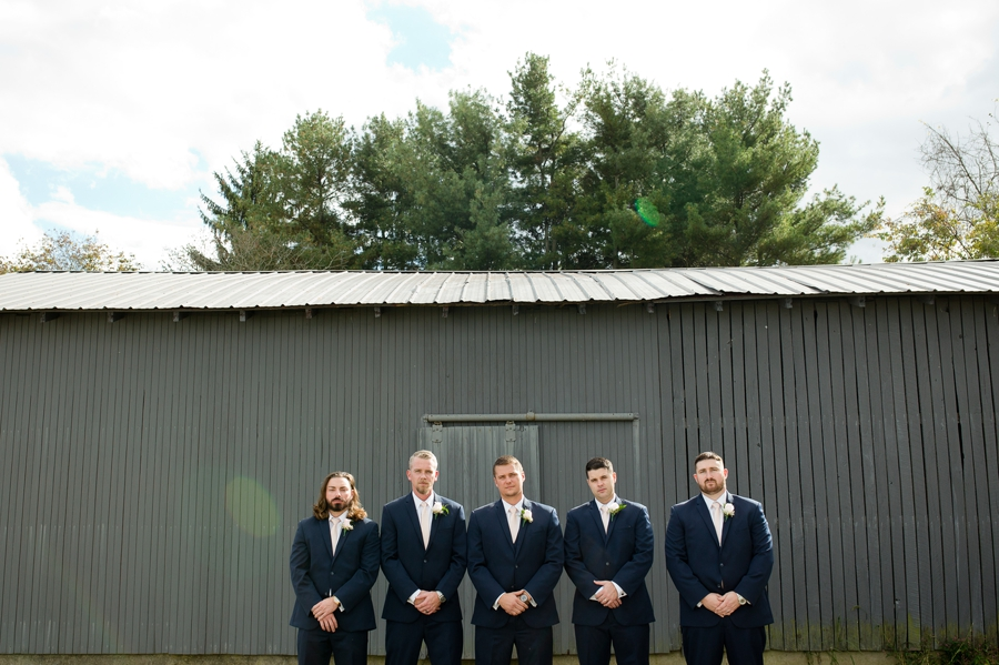 wide photo of groomsmen and groom at barn wedding in ohio