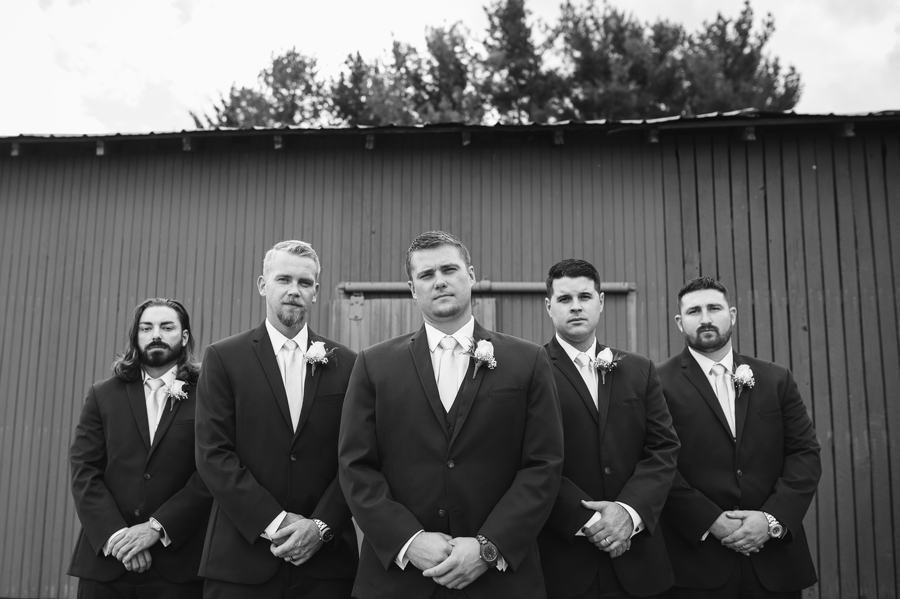 black and white photo of groom and groomsmen not smiling in front of a barn