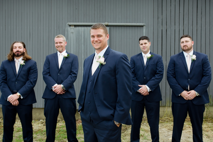 groom smiling with groomsmen in background at a barn wedding in ohio
