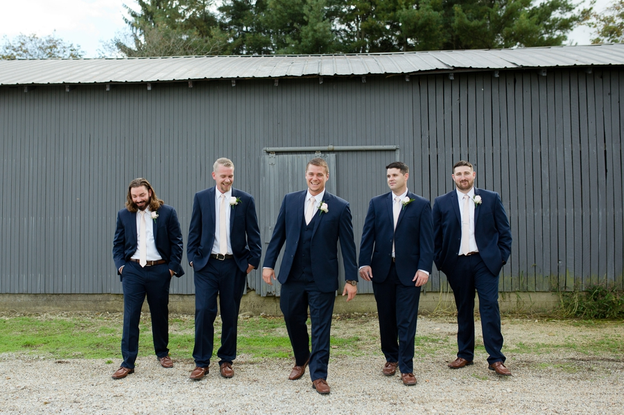 groomsmen in navy blue suits walking