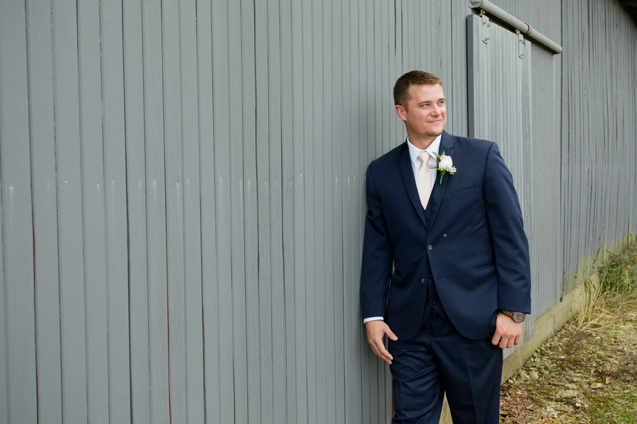 groom leaning on barn at a barn wedding in ohio