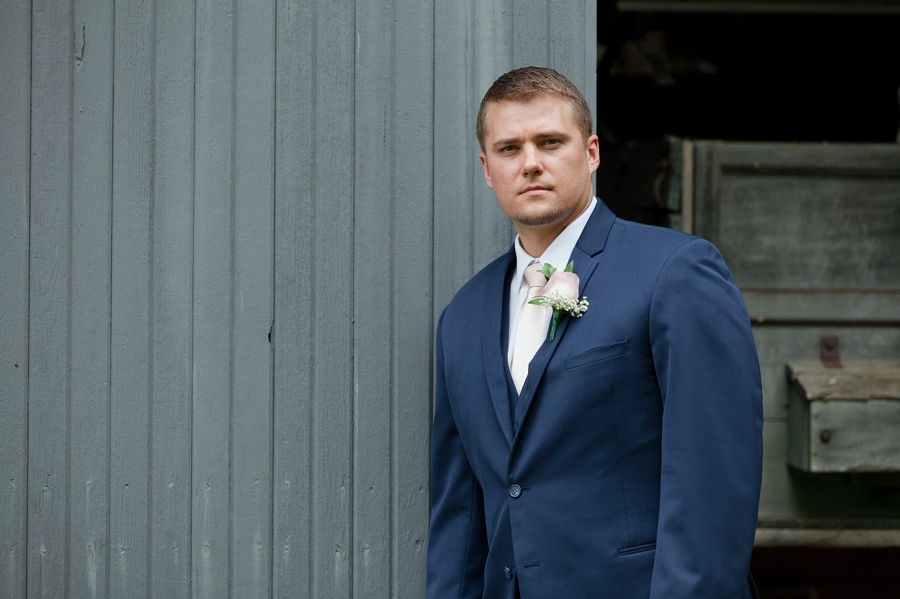 groom in navy blue suit with pink tie