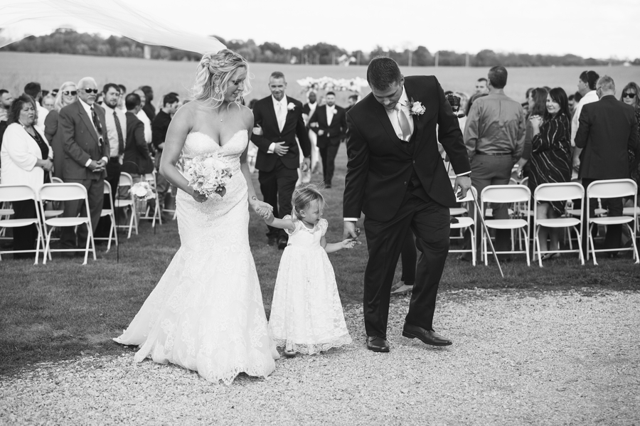 bride and groom with daughter during ceremony recessional