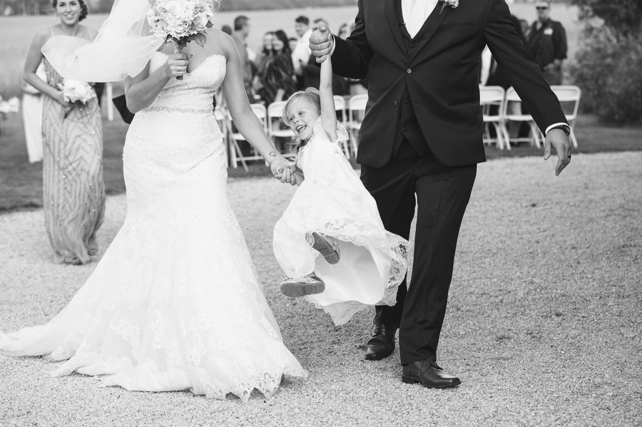 bride and groom lifting up daughter after wedding ceremony