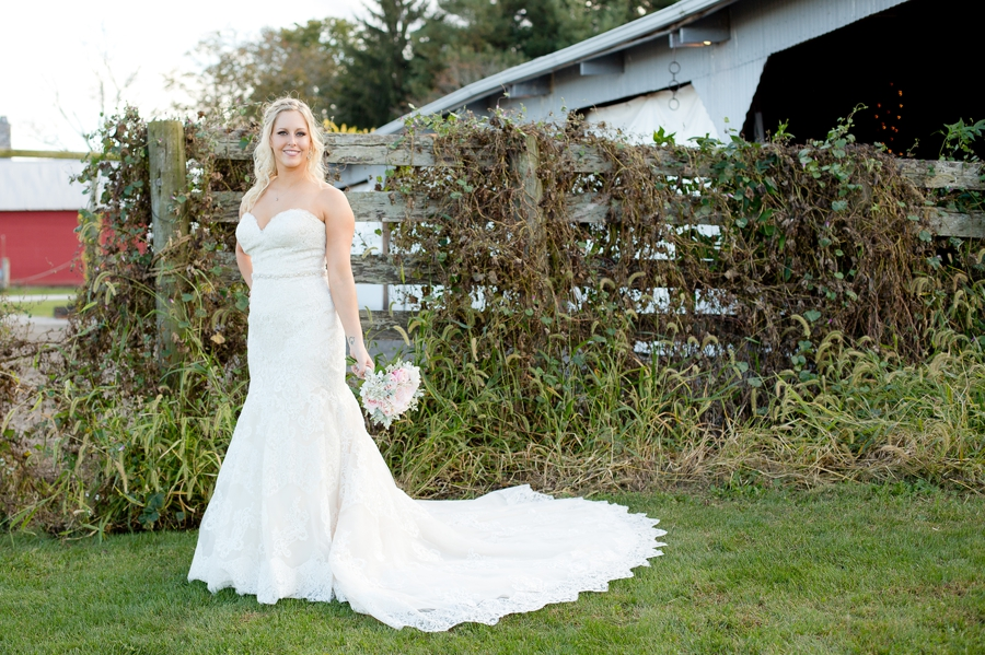 bride standing in front of barn covered in ivy