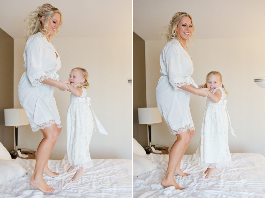 bride and daughter jumping on bed in hotel