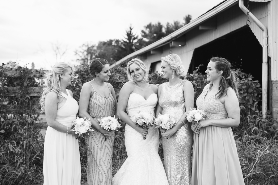 black and white photo of bridemaids looking at bride