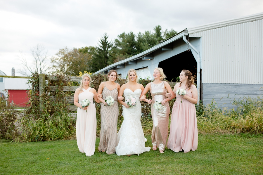 bride and bridemaids walking together in front of a barn
