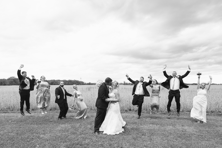 black and white photo of wedding party jumping in the air