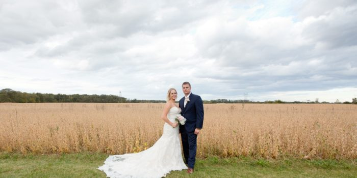 wide photo of a bride and groom in a field at a barn wedding in ohio