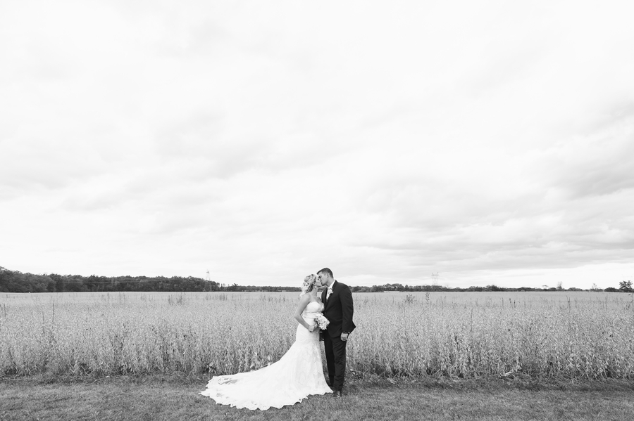 wide black and white photo of married couple kissing