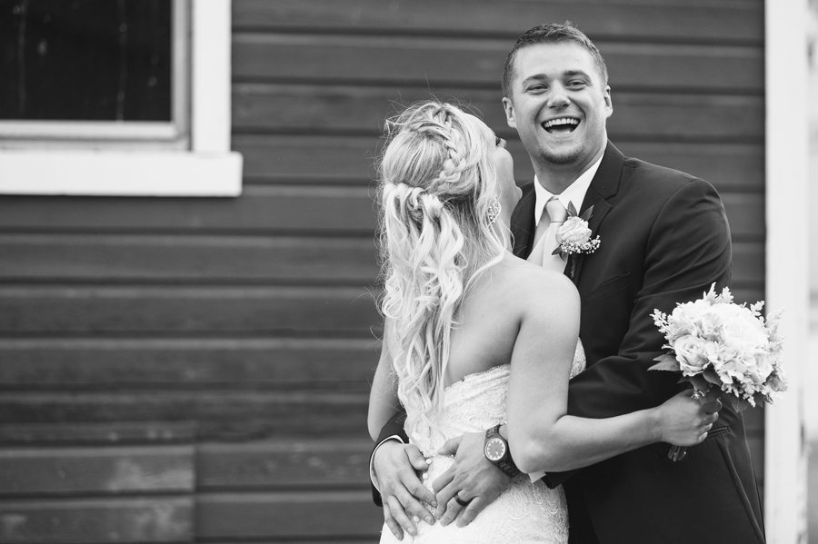 groom laughing in front of barn