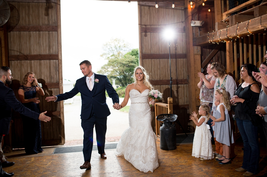bride and groom being introduced into reception of a barn wedding