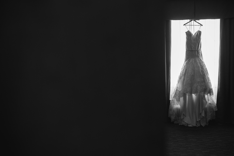 black and white photo of wedding dress hanging in window