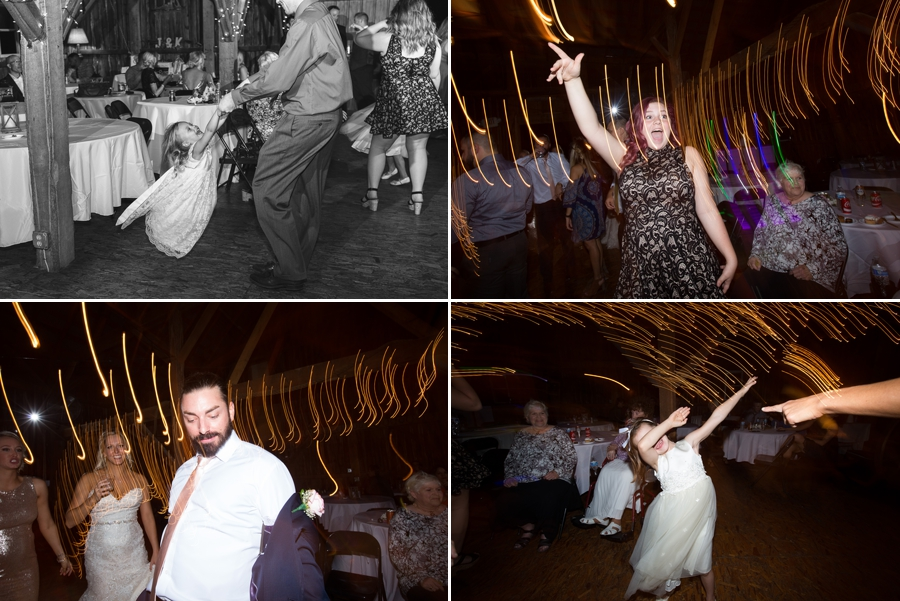 wedding guests dancing at reception in a barn